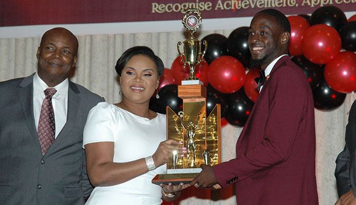 Jereem Richards receives the Athlete of the Year Award from Minister of Sports and Youth Affairs Shamfa Cudjoe while 1976 Olympic gold medallist Hasely Crawford looks on during the 2018 NAAA National Awards Ceremony held at Radisson Hotel, Wrightson Road, Port-of-Spain yesterday.