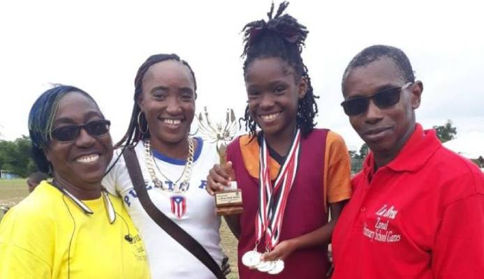 La Brea RC athlete, Chelcia Joseph (second from right), shows off her Girls U-11 Victrix trohpy and four gold medals (long jump, 100m, 200 and 4x100m relay) at her zone's Primary Schools' Track and Field Championships at Sobo Recreation Ground on February 14. She is joined by (left to right) La Brea RC teacher Sharnol Smith-Small, mother Mitchelle Joseph and principal Leon Charles. - Chequana Wheeler