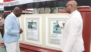1976 Olympic Gold Medallist Hasely Crawford, left, view the Wall of Fame with San Fernando Mayor Junia Regrello after the unveiling ceremony at the Harris Promenade Bandstand in San Fernando, yesterday.  TONY HOWELL